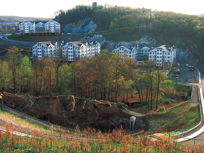 A view of several townhouses and condominium buildings on a hillside with retaining walls and leveled ground.